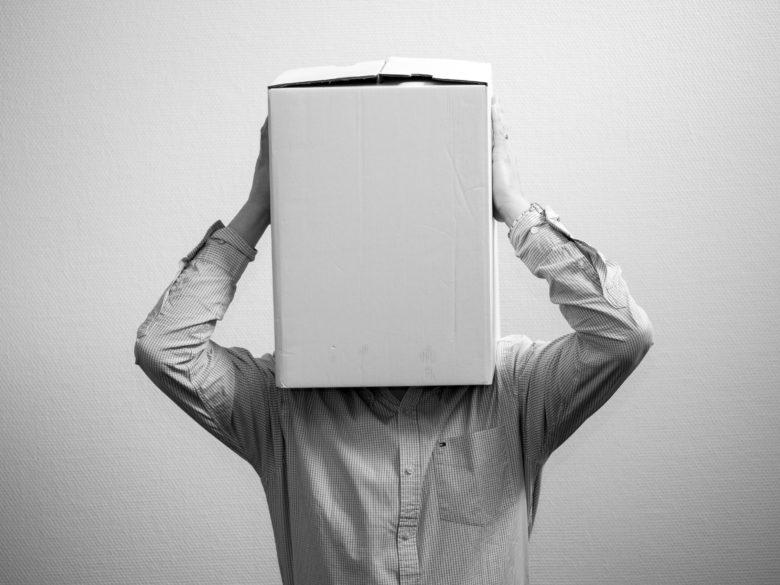 Ein Mensch stülpt einen Pappkarton über sein Gesicht. Foto: Ante Hamersmit / Unsplash