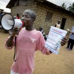 Matthew Zawalo hält in einer Hand ein Megaphon, in der anderen ein Plakat. Er arbeitet als Community Health Worker in Liberia. Auf dem Markt des Dorfes Busie wirbt er für eine Infoveranstaltung über das Corona-Virus. Foto: Christoph Pueschner/Brot für die Welt